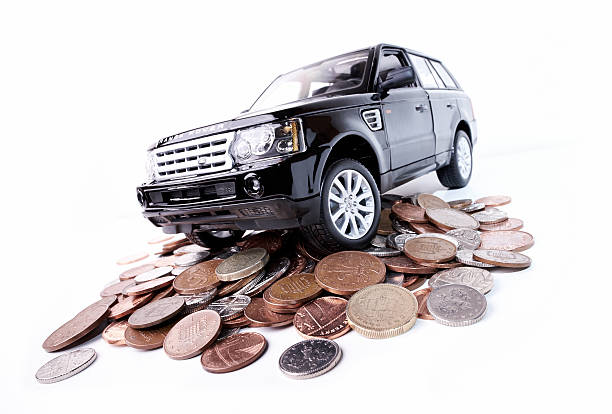 The High Cost Of Motoring Beaconsfield, UK - September 12, 2014: A model of a black Range Rover Sport sitting on a pile of coins against a bright white background. range rover stock pictures, royalty-free photos & images