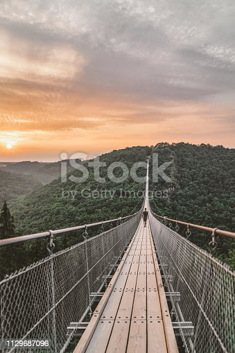 Photo of young Man walking on a hanging bridge in germany during the summer day, Geierlay suspension rope bridge. Lonely Young Man standing alone outdoor and admiring view Travel Lifestyle concept with lrope bridge background and sunset.