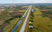 Aerial view of the highway LA-82 on the swamp nearby Grand Chenier, Louisiana, USA, in autumn.\nExtra large stitched panorama.