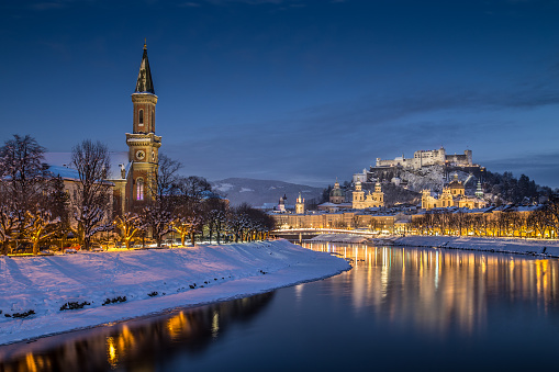 Beautiful view of the historic city of Salzburg with Salzach river in winter during blue hour, Salzburger Land, Austria.
