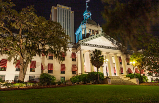 The Historic Florida State Capital building with flags flying, sits brightly lighted and surrounded by well maintained landscaping, seen here in the late evening with the modern State House and Senate Legislative Office Building rising in the black sky be