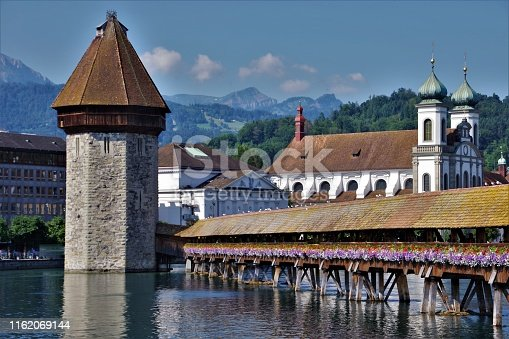 A series of four images of Switzerland's world famous Kappelbrucke (Chapel Bridge) in Luzern taken in high summer 2019. The bridge is the oldest wooden covered bridge in Europe and one of the oldest surviving truss bridges of its kind in the world. It dates originally from 1333 and was completed in 1365 form when it stood until 1993 when it was almost totally destroyed by an accidental fire. In view of its historical significance and status as one of Switzerland's premier tourist attractions, it was restored to its former glory by specialist artisans, woodworkers and carvers and archeaologists over two years and re-opened in 1995. It is a toll-free pedestrian footbridge that cuts diagonally across the River Reuss at the Head of Lake Lucerne (Vierwaldsattersee) linking the old town with the more modern side of the city, dominated by the Bahnhof Plaza and Quay on the opposite bank. Always adorned with flowers in window boxes planted along its length, this iconic, picturesque monument symbolises Switzerland and Swiss Culture as well as being one of the most attractive built structures on the planet. These four images are all of the bridge and its environs. This third image is more telephoto than the second and it includes a close-up of the tower with the detail of the Jesuit Baroque Church now clearly visible on the centre-right of the picture.