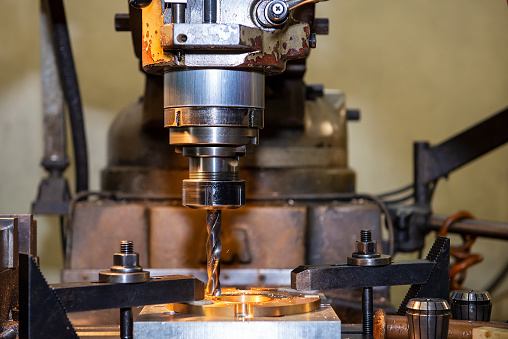 The hole drilling processing by drill tool on NC milling machine. The shop floor operation by NC milling machine.