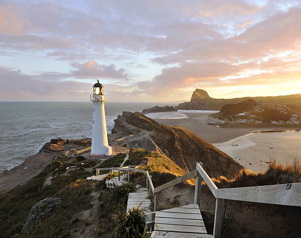 The Holiday Light Dramatic golden sunset beams illuminate the Castle Point Lighthouse - it is near the village of Castlepoint in the Wellington Region of the North Island of New Zealand. wellington new zealand stock pictures, royalty-free photos & images