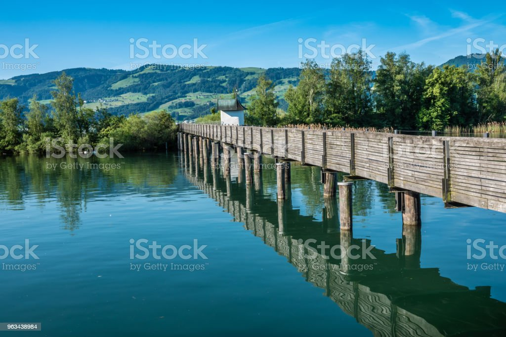 The Holzsteg, a wooden pedestrian bridge crossing the Zurich Lake (Obersee) at its narrowest point  Part of the eastern branch of the Way of Saint James - Zbiór zdjęć royalty-free (Alpy)