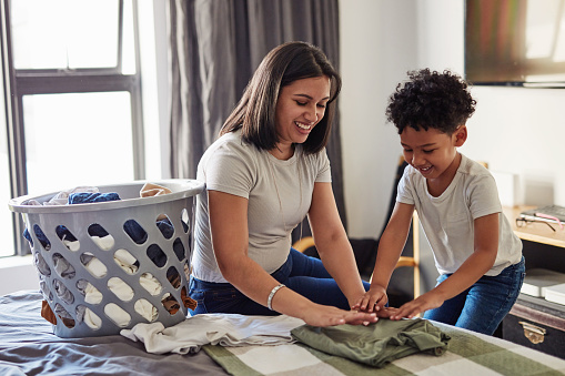 Shot of a young mother sitting on a bed helping her your son fold laundry