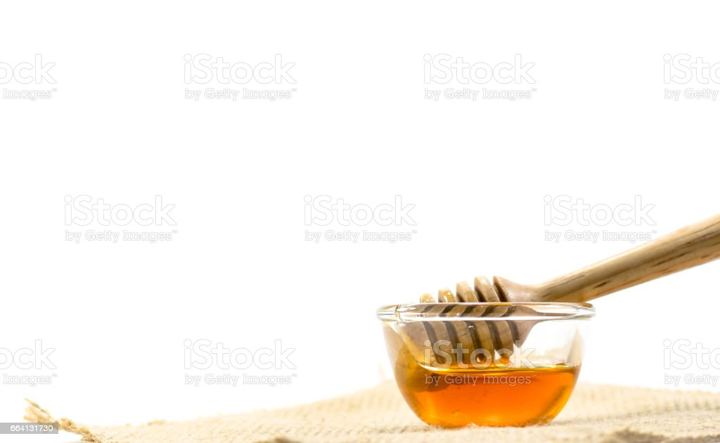 the Honey dipper and fragrant honey into a transparent bowl isolated white background. foto stock royalty-free