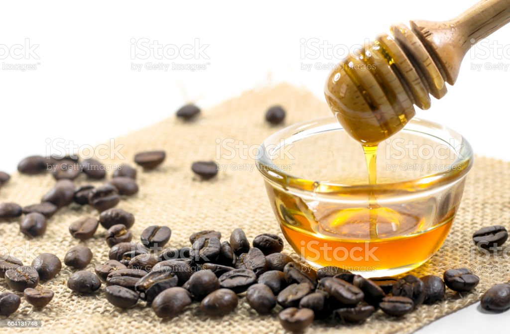 the Honey dipper and fragrant honey into a transparent bowl with coffee bean isolated white background. foto stock royalty-free