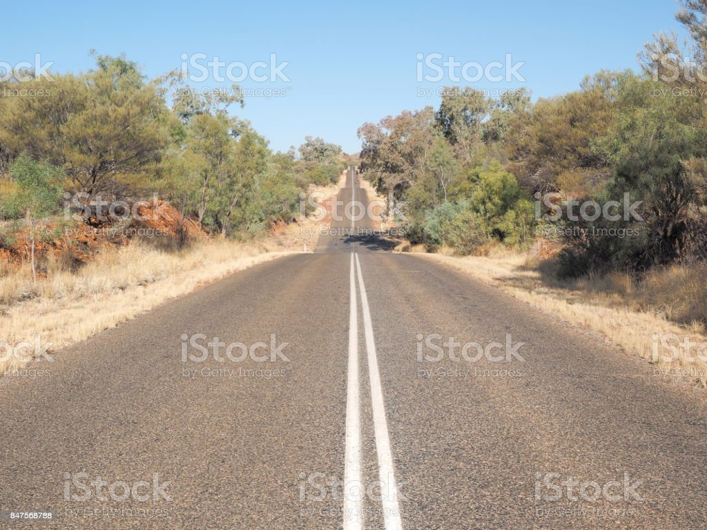The hot bitumen road to the horizon at Larapinta Drive, west MacDonnell ranges stock photo