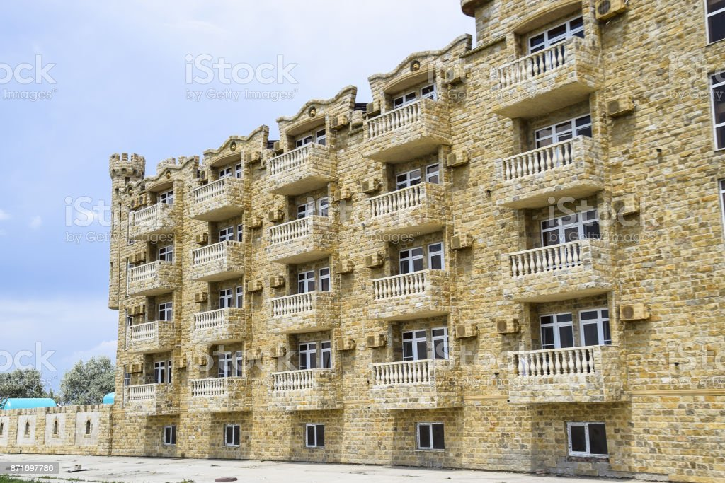 The hotel building, covered with decorative stone. Multi-storey hotel with a decorative trim, which is called Dagestani stone stock photo