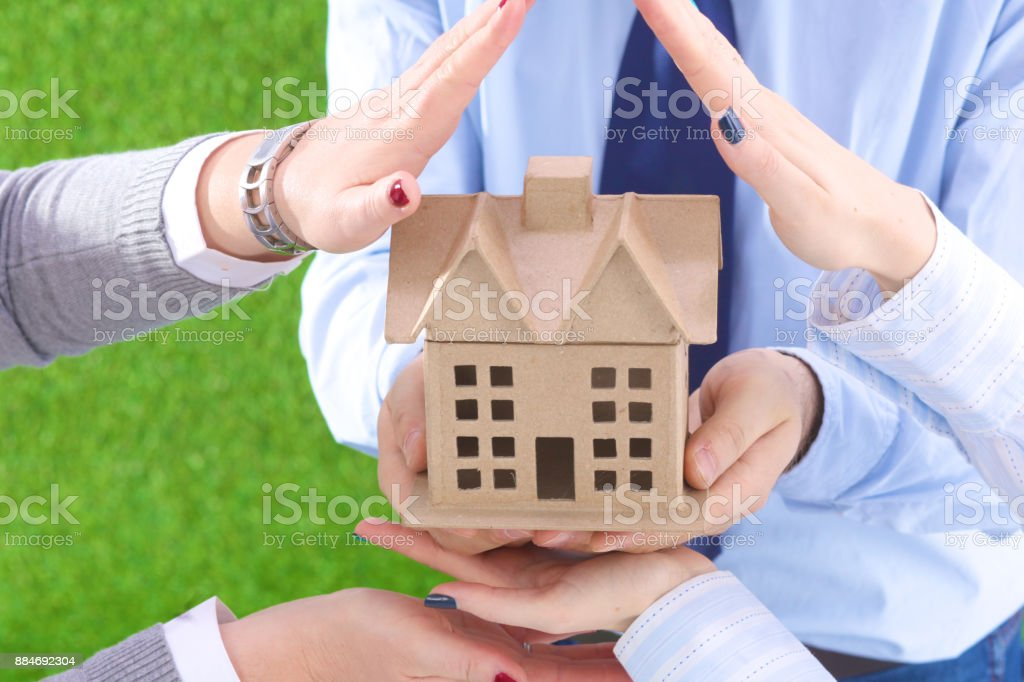 The house is in the hands of men and women on a grass background stock photo