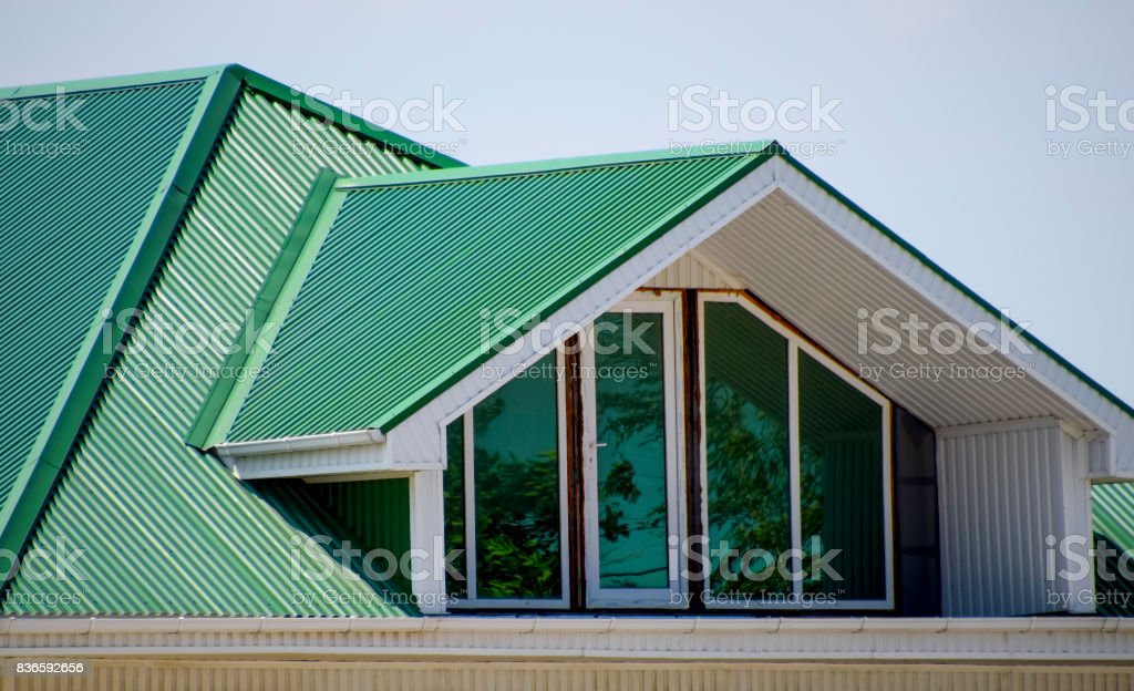 The house with plastic windows and a green roof of corrugated sheet. Green roof of corrugated metal profile and plastic windows. stock photo