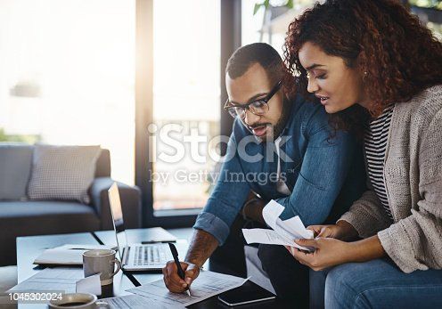 Shot of a young couple planning their budget together at home