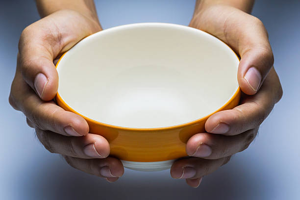 The hungry female holding an empty bowl on white background. stock photo