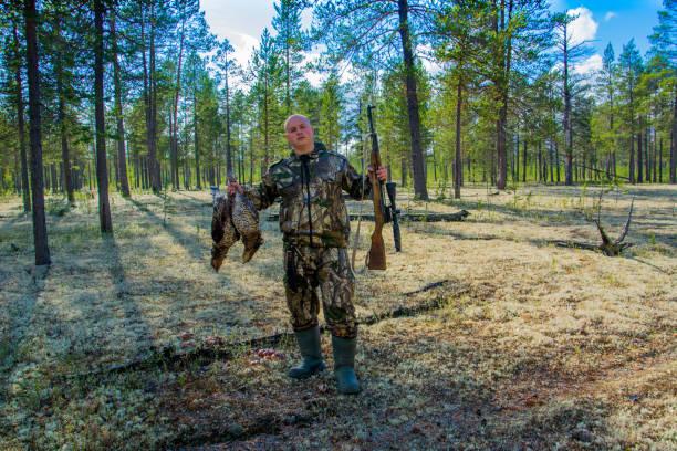 jägaren sitter med gevär och wildfowls. jakt på tjäder. - tjäder bildbanksfoton och bilder