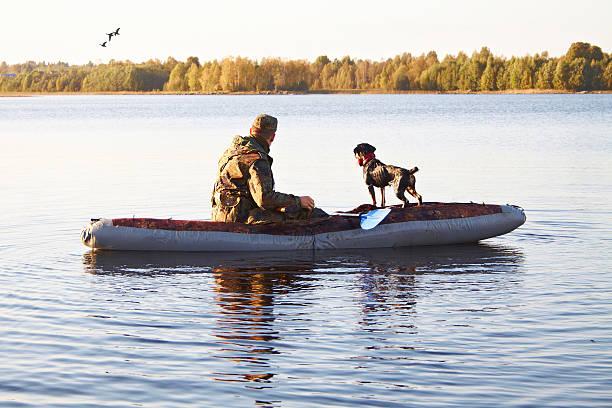 La sala hunter con un perro en el barco en el medio del lago - foto de stock