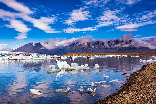 The ice floes of lagoon Jokulsarlon Cirrocumulus magically reflected in the water of lagoon. The concept of northern extreme tourism. The ice floes and cirrocumulus clouds of lagoon Jokulsarlon, Iceland glacier lagoon stock pictures, royalty-free photos & images