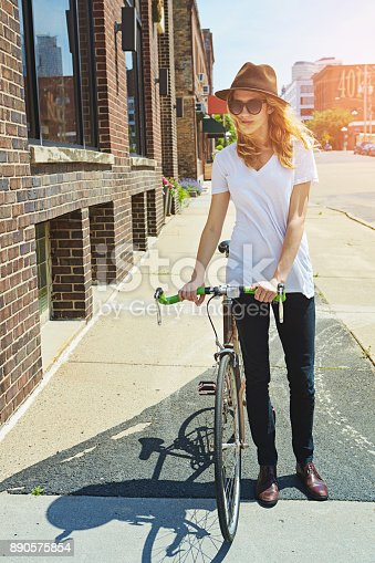 Shot of a young woman riding a bike in the city