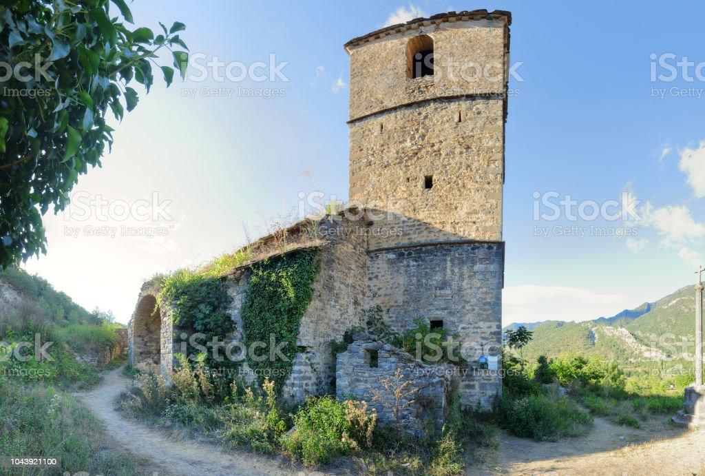 La iglesia de Iglesia de San Miguel y la torre del campanario cubierto con hiedra en Janovas, una aldea arruinada en el Pirineo aragonés de escalada abandonaron durante los años sesenta debido a la construcción de una presa - foto de stock