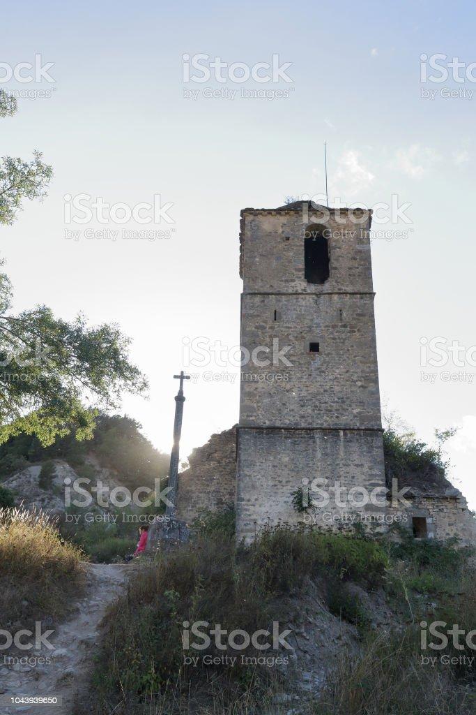 El Calvario iglesia de Iglesia de San Miguel y la torre del campanario cubierto con hiedra en Janovas, una aldea arruinada en el Pirineo aragonés de escalada abandonaron durante los años sesenta debido a la construcción de una presa - foto de stock