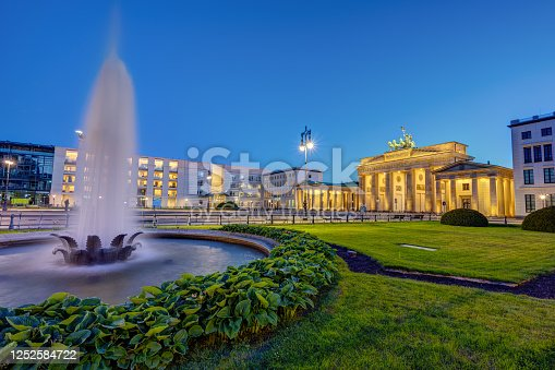 The illuminated Brandenburg Gate in Berlin at dusk with a fountain