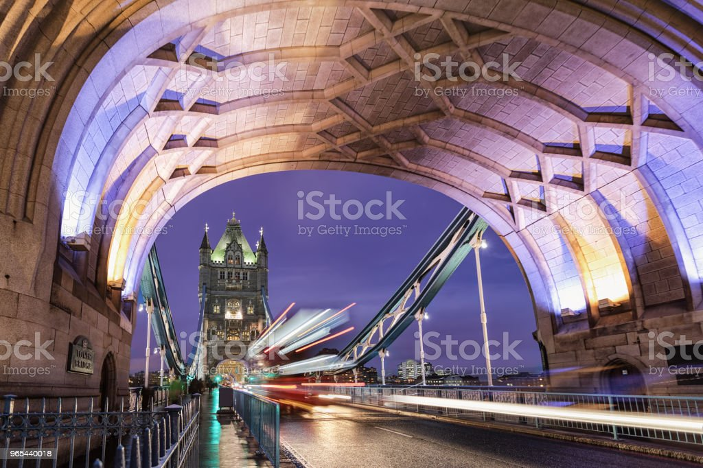 The illuminated Tower bridge during night with a passing by red double decker bus royalty-free stock photo