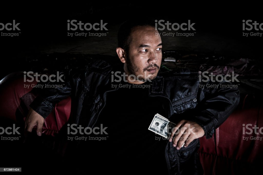 The image of a man who looks like a mafia, drug dealers who have money in hand. stock photo