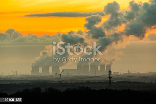 The imposing cooling towers of a power station near the village of Drax in North Yorkshire.  Plumes of water vapor leave a trail in the cold November night air.   Horizontal.  Space for copy.