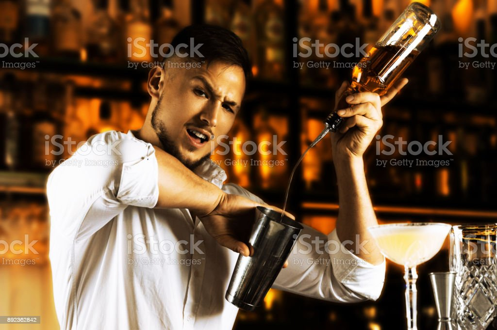 The incendiary bartender beautifully pours alcohol from the bottle into the shaker and arranges for his guests the present flaring of the show. stock photo