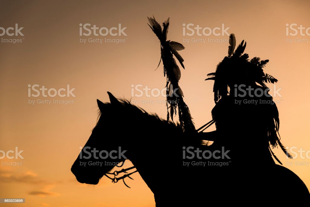 The Indians are riding a horse and spear ready to use In light of the Silhouette stock photo