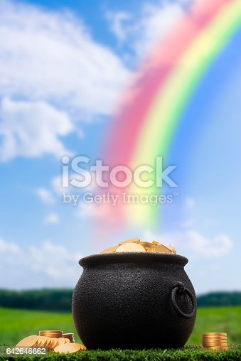 A black cast iron pot full of gold coins sitting in the grass at the end of a rainbow. Some gold coins are stacked on the grass next to the pot. Mythology says it is the secret hiding place of an Irish Leprechaun's pot of gold, some even say he is tricky.