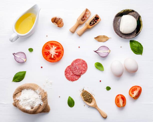 de ingrediënten voor de huisgemaakte pizza met ingrediënten zoete basilicum, tomaat, knoflook, laurier, peper, ui en mozzarella kaas op witte houten achtergrond met flat lag. - ingrediënt stockfoto's en -beelden