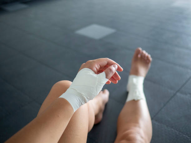 The injured athlete- athlete with thumb and ankle injuries and tape jobs stock photo