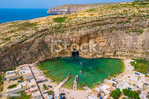The Inland Sea and tourist boat. Dwejra is a lagoon of seawater on the island of Gozo. Aerial view of Sea Tunnel near Azure window. Mediterranean sea. Malta country