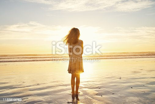 Rearview shot of a young girl standing on the beach