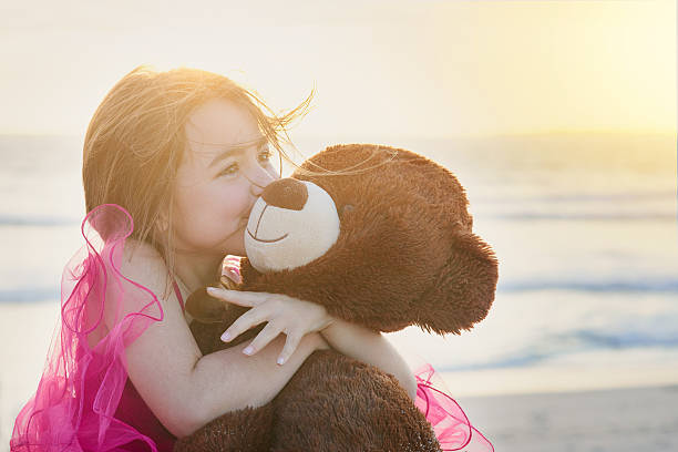 The innocence of childhood Portrait of a cute little girl playing with her teddy bear on the beach teddy bear stock pictures, royalty-free photos & images