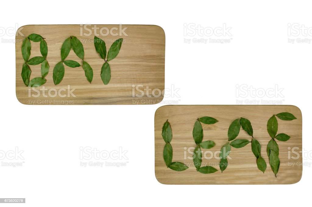 The inscription, a laurel leaf, on a cutting board, is made with leaves. stock photo