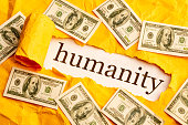 istock the inscription humanity is seen through torn orange paper around the scattered money 1248080586