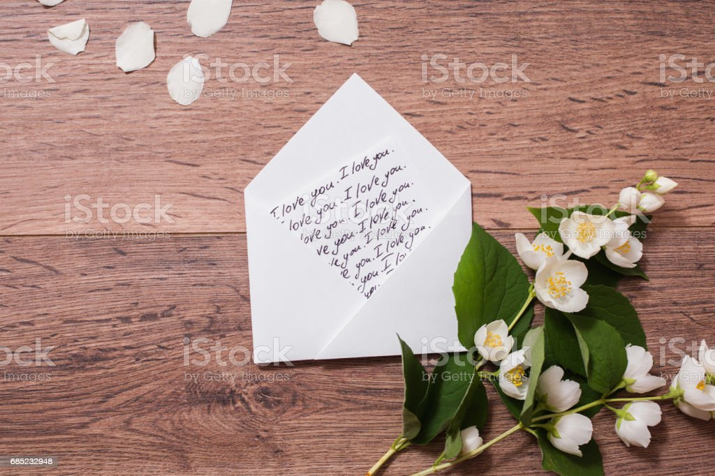 The inscription 'I love you' writing on the envelope calligraphy. Flowers and jasmine petals on wooden background. Greeting card. Conceptual photography. Wedding invitation card. Valentine day.; royalty-free stock photo