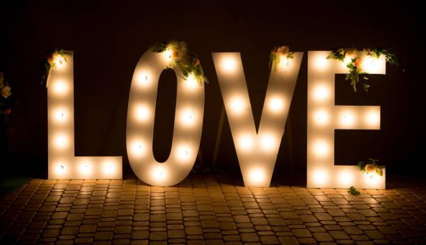 die inschrift ist liebe. leuchtende große buchstaben. hochzeitsdekorationen. - heiratssprüche stock-fotos und bilder