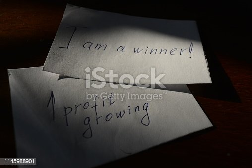 1164401366 istock photo The inscription on paper is I am a winner with profit growing and a lot of papers on business wooden lacquered table 1145988901