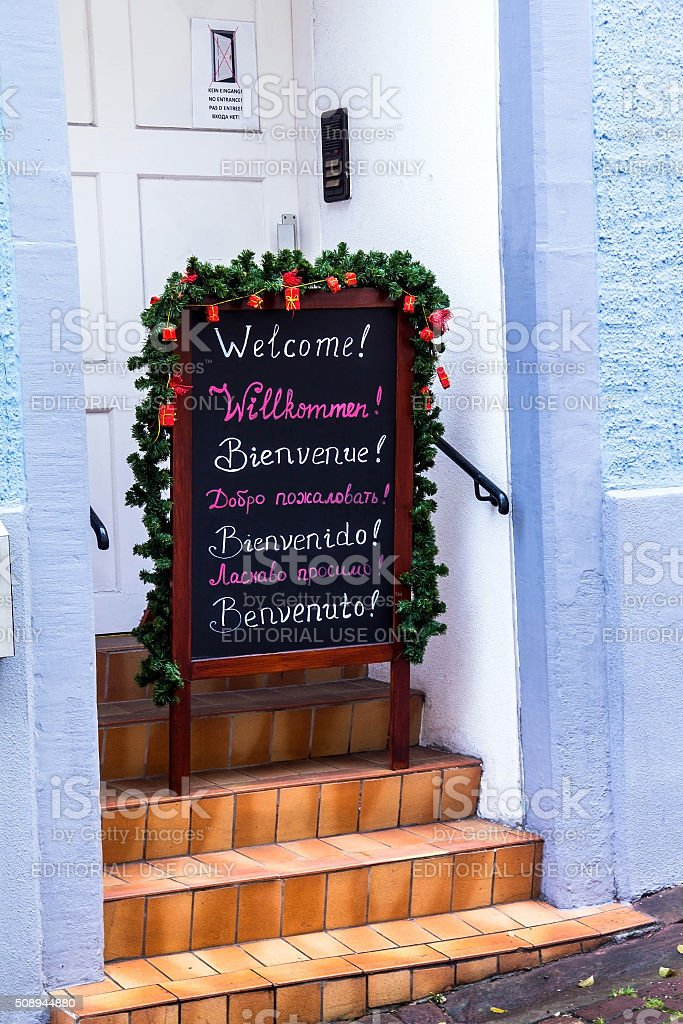 The inscription WELCOME 7 language on a black chalkboard stock photo