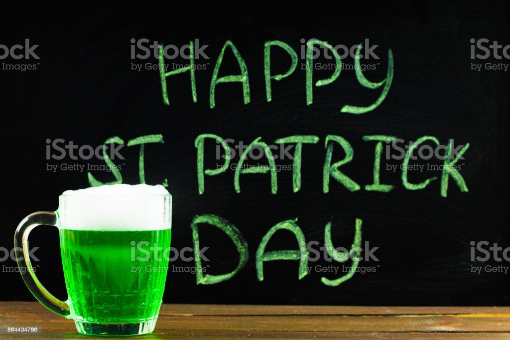 The inscription with green chalk on a chalkboard: Happy St. Patrick's Day. A mug with green beer. – zdjęcie