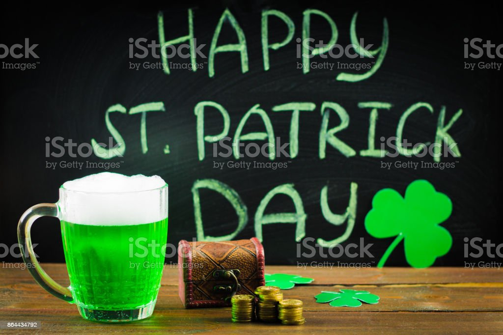 The inscription with green chalk on a chalkboard: Happy St. Patrick's Day. Clover leaves. Chest with coins. A mug with green beer. – zdjęcie