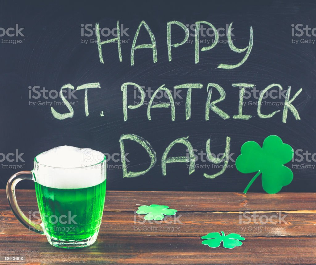 The inscription with green chalk on a chalkboard: Happy St. Patrick's Day. Clover leaves. A mug with green beer. – zdjęcie