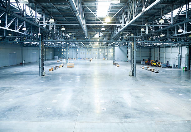 the inside of a large and empty modern warehouse - cement floor stock photos and pictures