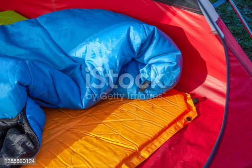 The inside of a red tent with an blue sleeping bag and an orange self-inflating blow-up mattress pad for under his sleeping bag