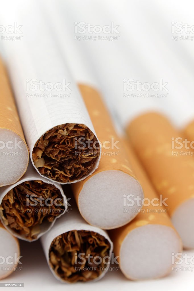 The insides of 3 cigarettes on a pile of cigarettes stock photo