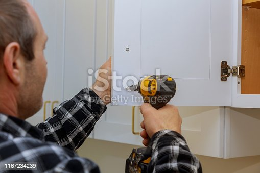 The installing a furniture handle process of assembling kitchen cabinet