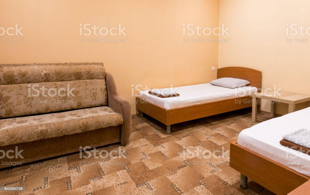 The interior of a small room with a sofa and two beds stock photo
